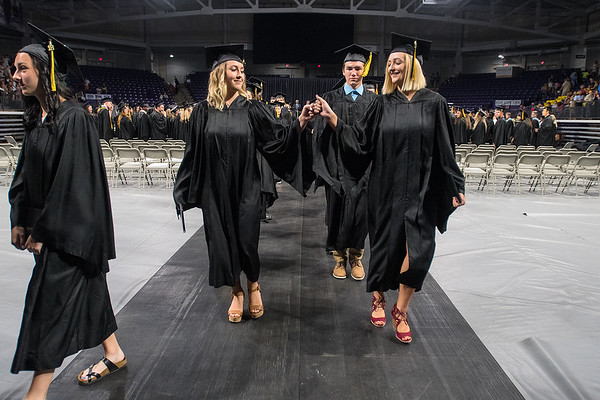Ally Kanzenbach (left) and Hailey Hoppe (right) fist bump as they exit Bresnan Arena at the end of the Mankato East commencement held on Friday. Photo by Jackson Forderer