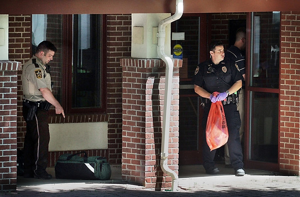 John Cross<br /> A North Mankato police officer (right) carries a bio-hazard bag from the entrance to the North Mankato Police Department.