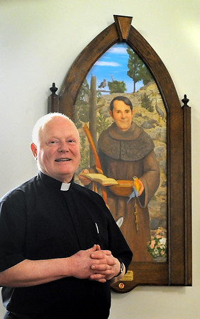 John Cross<br /> Father Bob Schneider stands in front of a painting and relic of St. Francis of Assisi.