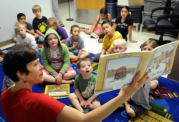John Cross<br /> Nancy Sizer, a kindergarten teacher at South Elementary School in St. Peter, reads a book to a young audience attending the Read and Feed summer reading program Tuesday at the St. Peter High School Cafeteria.
