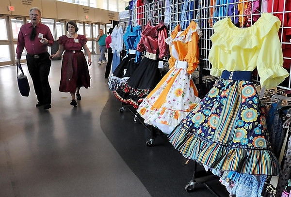 John Cross<br /> Participantsdof the 61st Minnesota State Sqaure and Round Dance Convention stroll past a display of dance fashions offered for sale.