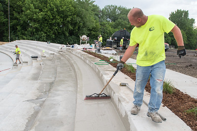 Dustin Jacobs (right) with Nielsen Blacktopping and Concrete spreads out concrete at the Vetterstone Amphitheater on Wednesday. The renovation will be finished just in time for the Three Dog Night concert on Friday. Photo by Jackson Forderer