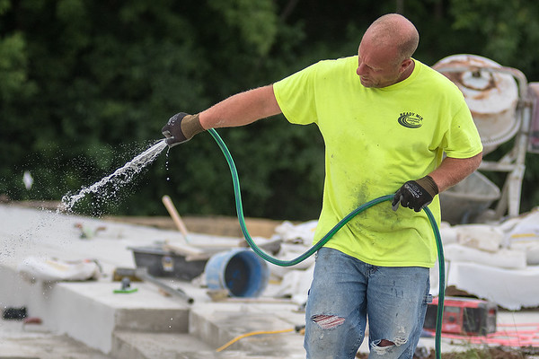 Dustin Jacobs waters down some newly poured concrete at the Vetterstone Amphitheater on Wednesday. Photo by Jackson Forderer