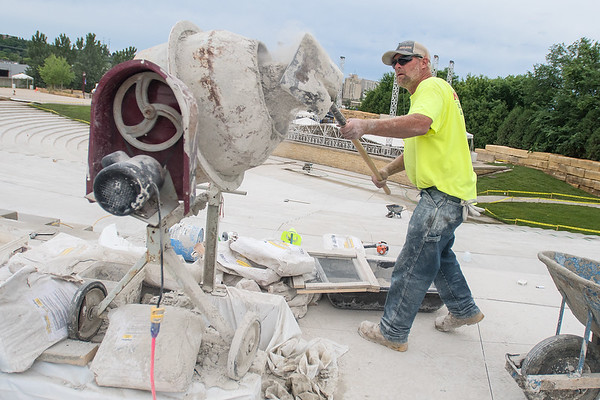 Jason Anderson with Nielsen Blacktopping and Concrete adds concrete powder to a mixer on the top row of the Vetterstone Amphitheater. The finishing touches on the newly renovated amphitheater are being made before the Three Dog Night concert to be held on Friday. Photo by Jackson Forderer