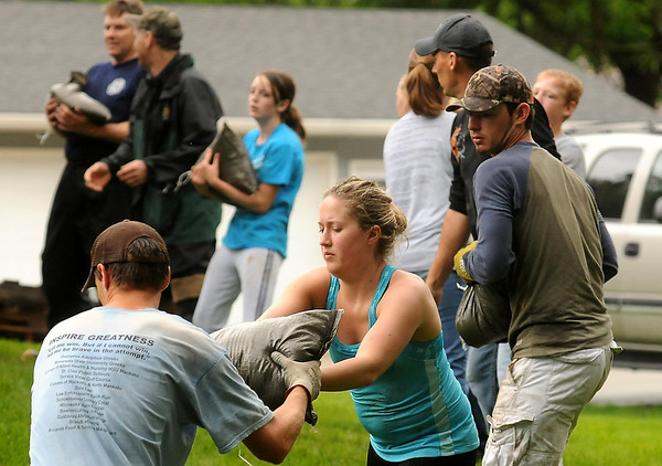 Volunteers pass sandbags along a human chain to protect homes in St. Clair from rising waters on the nearby Le Sueur River on Thursday. Photo by John Cross