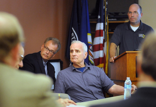 Governor Mark Dayton is briefed on the effects of recent severe weather and heavy rain in south-central Minnesota during a visit to Mankato on Thursday. Mankato City Manager Patrick Hentges (left) and Blue Earth County Deputy Director of Emergency Management are pictured behind him. Photo by John Cross