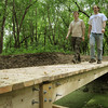 Paul Hanson (left) and Dan Oachs walk across a bridge that was constructed as part of a trail system they have created along the Minnesota River near the Traverse de Sioux treaty site north of St. Peter. John Cross photo