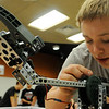 Brandon Egenes makes some adjustments to the robot his was helping assemble during a Robotic Challenge Camp at SCC on Tuesday. Photo by John Cross
