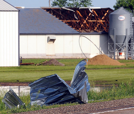 Twisted metal from a nearby building rests on the shoulder of Highway 22 south of Mankato. Several machine sheds on area farms were damaged by high winds on Monday near Mapleton. Photo by John Cross