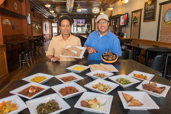 Dermi (left) and Lencho Jarso, the new owners of Savoy, stand behind a smorgasbord of Ethiopian and Greek food. Demi is holding a plate of Engera, or Ethiopian bread. Lencho is holding a skillet of seasoned lamb. Photo by Jackson Forderer