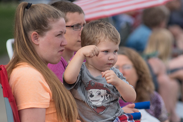 Blake Goossen, 3, of St. Clair, pretends to direct the St. Peter High School marching band while sitting on Brittany Goossen's lap at the Battle of the Bands held in Lake Crystal. Photo by Jackson Forderer