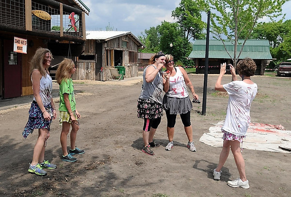 Participants in the Mankato Zombie Run take pictures near the newly relocated buildings on the McGowan farm Saturday. Photo by Pat Christman