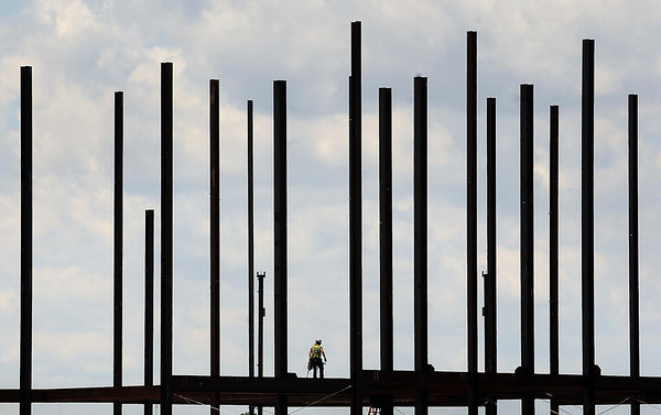 A steel worker is dwarfed by an iron architectural Stonehenge as he works on the seven-story office complex that is being constructed along South Riverfront Drive in Mankato. Photo by John Cross