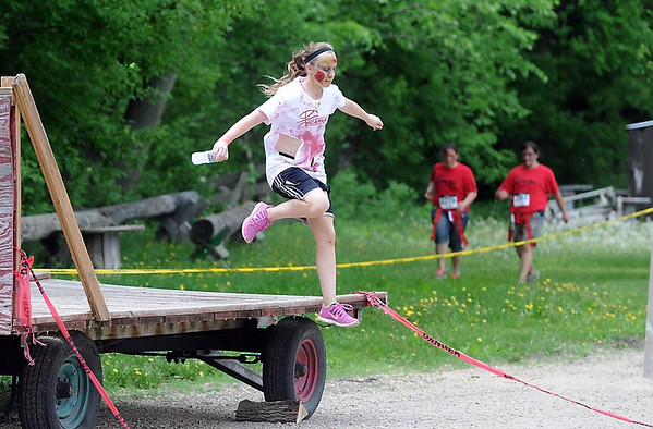 Amber Frederick leaps over a hay wagon during the Mankato Zombie Run Saturday at the McGowan Farm.  Photo by Pat Christman