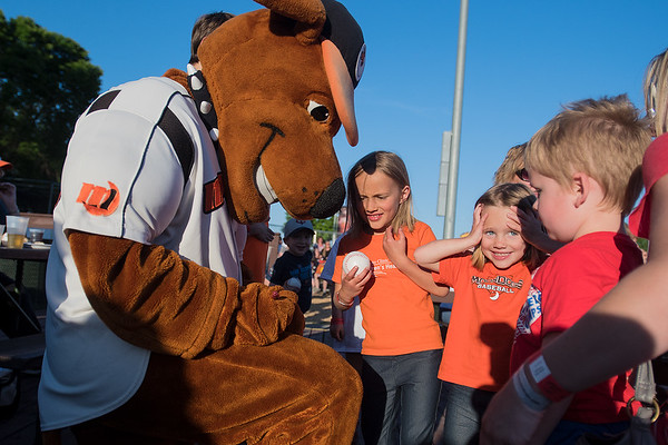 Mankato Moondogs mascot Muttnik signs baseballs for Alayna Mickelson, 5, (center) and Amelia Mickelson, 3, (second from right) at the home opener on Wednesday at Franklin Rogers Park. Photo by Jackson Forderer