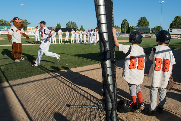 Ball boys Carson Hart, 8, (right) and Micah Beckendorf, 9, (second from right) watch the introductions for the Mankato Moondogs as Muttnik the mascot high fives the players on Wednesday at Franklin Rogers Park. The Moondogs played their home opener against the Rochester Honkers. Photo by Jackson Forderer