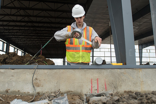 Phil Hasselquist pulls off a piece of duct tape while working on the new Medieval Chasis building on Technology Drive. Photo by Jackson Forderer