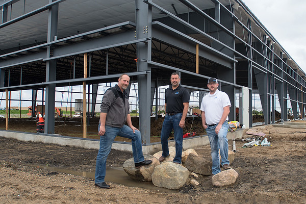 Jim Halbur (left) with Coldwell Banker Commercial, Ryan Evenson (center) with APX Construction Group and Joey Barr (right) also with APX outside of a new commercial building being constructed on Technology Drive. Halter and Evenson are the owners of the building. Photo by Jackson Forderer