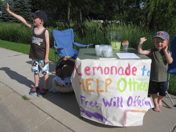 Photo by Katie Mons<br /> Eli, 5, Charlie, 2 months and Jack, 2, stood along Le Sueur Ave. in Eagle Lake Monday from 5 to 6 p.m. waving cars down to help raise money for Royal Family Kids Camp, a camp being started in Mankato for abused and neglected children.