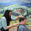 Hair stylist Courtney Voth trims Rodney Anton's hair.