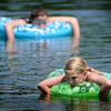 John Cross<br /> Friends Aubrey Larson (front) and Laura Franke found some heat relief Tuesday in a lazy drift across Hiniker Pond.