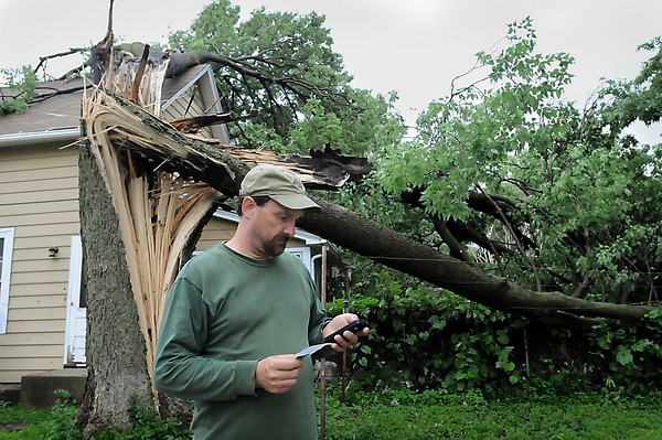 John Cross<br /> Darrin Johnson was trying to reach his insurance company after a tree landed on the roof of his rental property at 407 South Ave. during a storm that swept through the area early Friday morning.