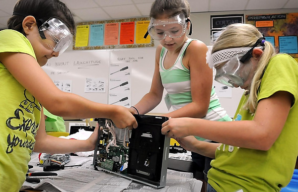 John Cross<br /> From left, Madi and Emma Doell and Lexi Johnson team up to delve into the innards of a Blue-ray player during a session of Camp Invention at Mankato East High School.
