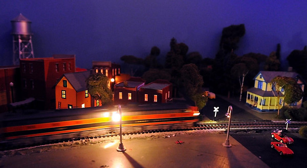 Pat Christman<br /> A model train runs past a nighttime scene of a town at the St. James Model Railroad Club's display Saturday.