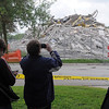 Pat Christman<br /> One of Gage's twin towers lies in a pile of rubble as spectators take pictures after its implosion Saturday.