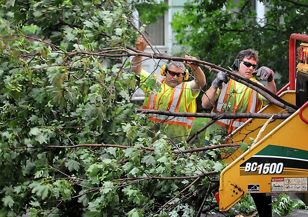 John Cross<br /> City of North Mankato workers feed limbs into a shredder during clean-up operations after a storm downed trees and power lines early Friday morning.