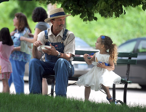 Pat Christman<br /> Dean Depuydt and his granddaughter Brie Anderson, 3, take a break from playing music to have some ice cream at the Betsy-Tacy Lawn Party & Lincoln Park Historic Home & Garden tour Saturday.