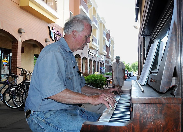 John Cross<br /> Jack McGowan plays a tune Thursday on a piano he just unloaded at University Square and placed near the Cold Stone Creamery. McGowan is placing old pianos around the community to inspire some spontaneous musicians to sit down and play.