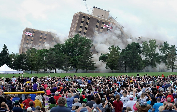 John Cross<br /> Thousands watch as Gage Towers on the Minnesota State University, Mankato campus collapse onto themselves seconds after series of strategic explosive charges were set off Saturday. The 12-story buildings which were the tallest in Mankato had served as residence halls since the mid-1960s.