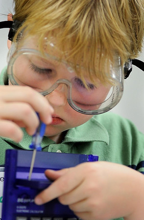 John Cross<br /> Jackson Kuiper wields a screwdriver to get into the heart of a calculator during a session of Camp Invention at Mankato East.