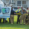 Emergency responders carry an accident victim by stretcher to a helicopter to be airlifted. A five-vehicle accident occurred on Highway 60 on Friday evening south of Madison Lake. Photo by Jackson Forderer