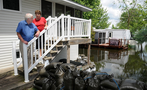 Brent and Judy Phillipson keep a wary eye on the water covering their RV park in Waterville on Monday. The Cannon River and Lake Tetonka rose steadily beginning late last week but the Phillipsons said the water hasn't risen since Sunday