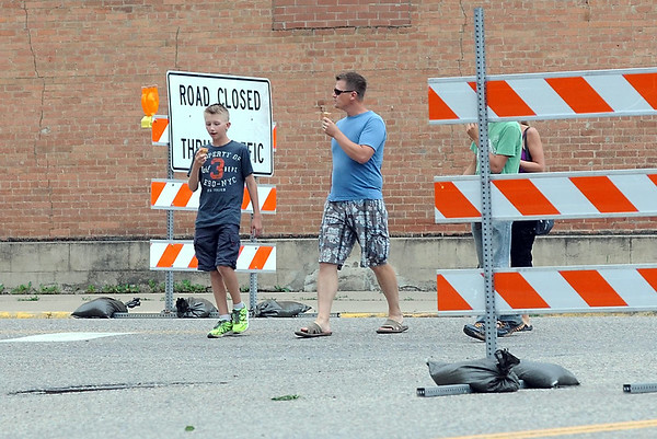 A family enjoys ice cream as they walk past barricades closing Highways 93 and 19 in Henderson during Sauerkraut Days Saturday. Photo by Pat Christman