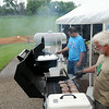 Former Henderson mayor Keith Swenson, right, and Luke Dvorak tend brats in the shadow of the levee holding back a flooded Minnesota River during Sauerkraut Days Saturday in Bender Park. Though the levee has done its job many roads in and out of Henderson remain closed after being damaged by mudslides. Photo by Pat Christman