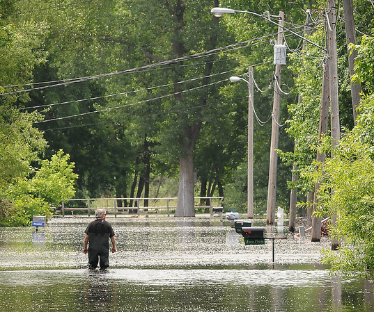 A man walks down a flooded street Monday to reach his property in the lagoons area of Waterville, on the shores of Lake Tetonka. Photo by John Cross