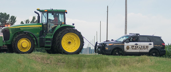 Gary Bartelt uses his tractor to tow a stolen Mankato police SUV out of his corn field on Thursday. Mankato police were led on a high-speed chase on Thursday, with speeds up to 130 miles per hour. The chase ended south of Waldorf after the suspect hit a set of spike strips and drove through Bartelt's field. Photo by Jackson Forderer