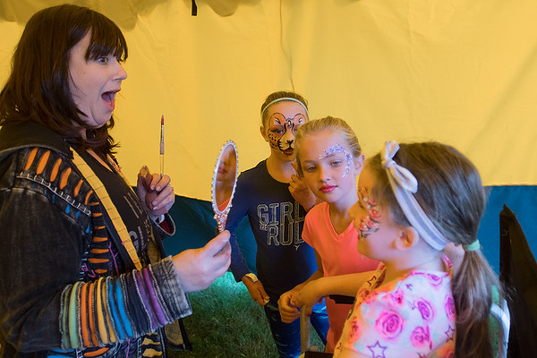 Jodi Gustafson (left) with Big Shoe Entertainment shows Breely Henning, 6, her new face paint as friends Ruby Marble (second from right), 9, and Lucy Smith, 9, look on at the Solstice Outdoor Music Festival held on Saturday. Photo by Jackson Forderer