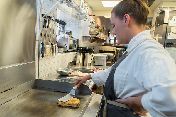 Laura Siefkes, cooks a smoked salmon grilled cheese sandwich in the kitchen at Tandem Bagels. Siefkes is part of the Chef and Farmer Collective, which will be serving a 10 course meal on July 7 at a pop up restaurant called The Gathering Table. Photo by Jackson Forderer