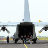 "Passengers sit outside the cargo door of ""Ernie,"" the Blue Angels' C-130 support aircraft before a flight Friday."