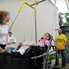 John Cross<br /> Rachael Nelson, who is in a wheelchair because of Rett Syndrome, is pushed in a special wheelchair swing by Nathan Herme (right) as her parents, MaryAnn and and Byron, look on. A fourth annual Bend of the River Cook-Out will be held June 28-29 to raise funds to purchase more of the adaptable playground equipment for area parks. For more information about the event, contact Herme at (507) 317-9291 or go to Mankatocookout.com.