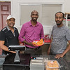From left, Abdella Namo, Mohamed Ahmed and Ahmed Musse behind the counter at Brothers Restaurant and Grocery. Ahmed holds a basket of sambusa, an African pastry filled with meat. Photo by Jackson Forderer