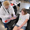 American Red Cross phlebotomist Paula Moerer takes blood from Cassidy Ekstedt's arm during a blood drive for injured former Minnesota State University football player Isaac Kolstad Tuesday at the Mankato National Guard Armory. Ekstedt played high school hockey with Kolstad's sister at Mankato East High School. Photo by Pat Christman