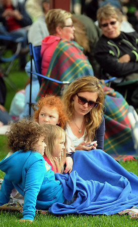 From front to back, Kadence, Harper and Avery Wilmes and Danika Jamieson wear a blanket to ward off a chilly breeze on Thursday at Songs on the Lawn. Photo by John Cross