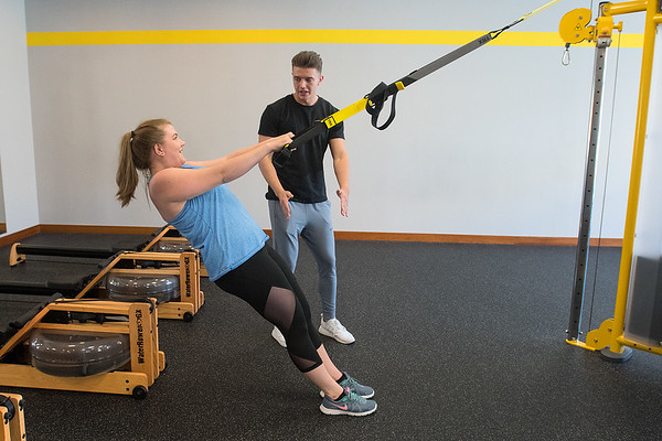 Mason Holecek instructs Alaena Klages during a high row exercise at JP Fitness on Wednesday. Holecek works as a personal trainer at the gym, which also offers small group exercise classes. Photo by Jackson Forderer