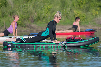 Annette Perry (center) and others hold a yoga pose on their paddle boards while taking a Bent River yoga class led by Betty Harsma (not pictures) at Red Jacket Park. Photo by Jackson Forderer