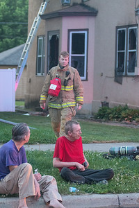 An unidentified man (red shirt) was pulled out of a house fire through a window at 118 Van Brunt by Mankato firefighters, as they responded to a call at 8:20 p.m. on Thursday. Photo by Jackson Forderer